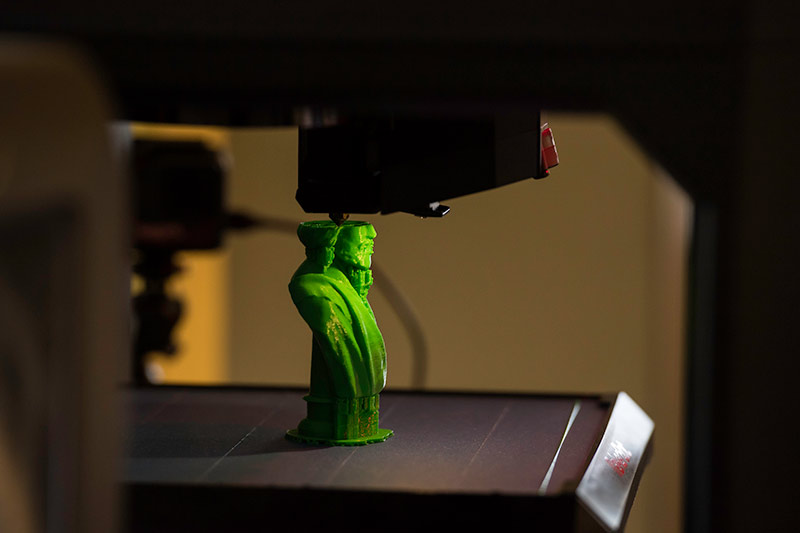 3d printer has created two-thirds of a small green statue of Frederick Douglass