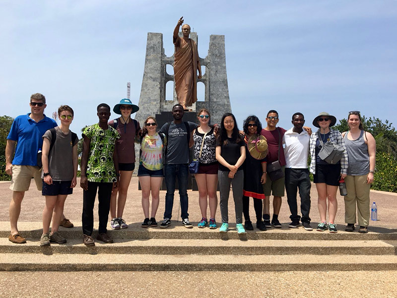 group of students posing in front of a large statue
