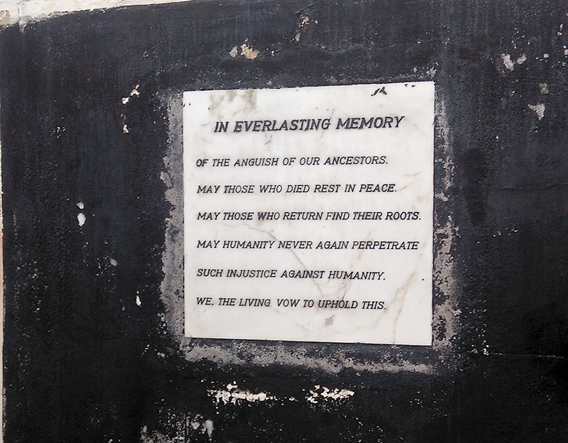 sign on a wall tha reads IN EVERLASTING MEMORY OF THE ANGUISH OF OUR ANCESTORS. MAY THOSE WHO DIED REST IN PEACE. MAY THOSE WHO RETURN RIND THEIR ROOTS. MAY HUMANITY NEVER AGAIN PERPETRATE SUCH INJUSTICE AGAINST HUMANITY. WE, THE LIVING, VOW TO UPHOLD THIS.