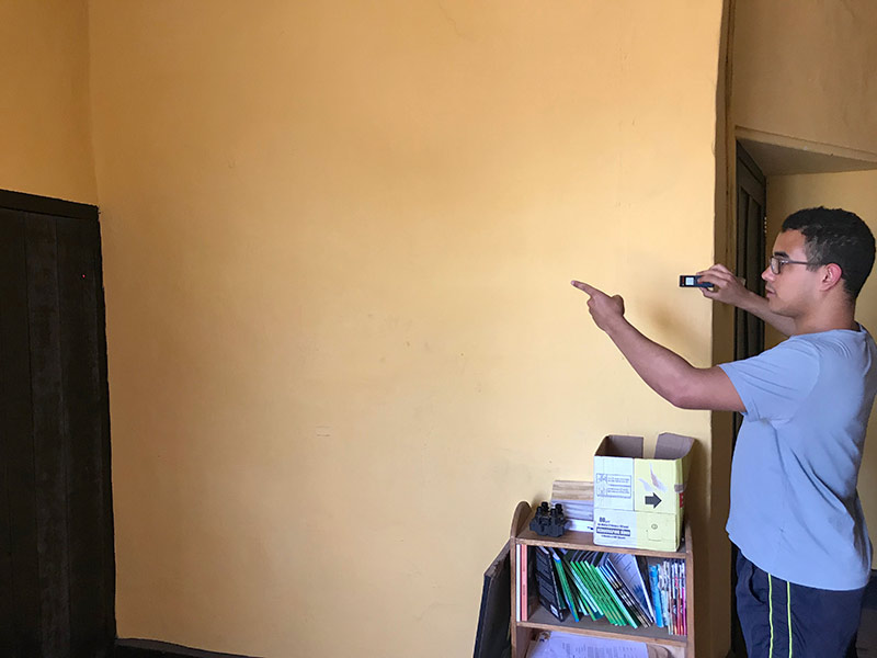 student holding an measuring instrument against a wall