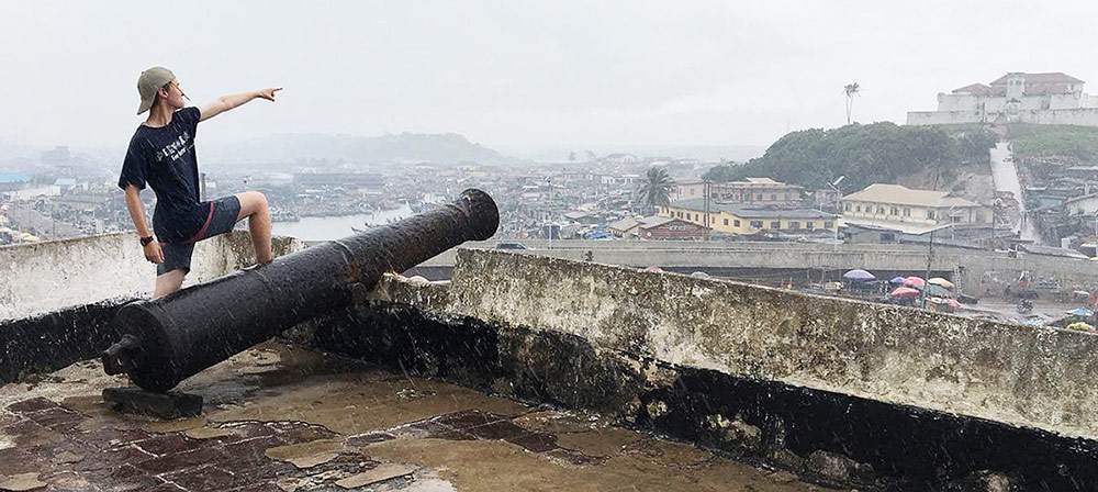 Ewan Shannon stands by a cannon, pointing to the town of Elmina from the rooftop of Fort Amsterdam