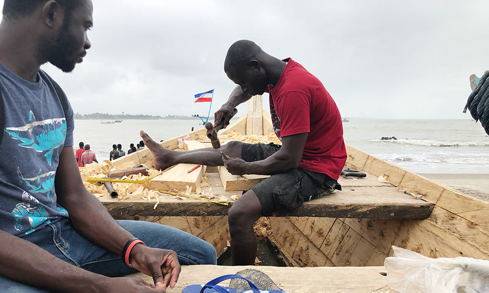 two men working on a wooden boat