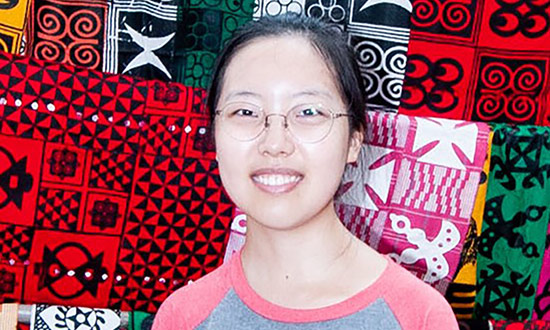 woman poses and smiles in front of colorful textiles