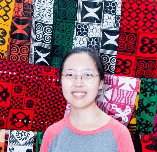 woman smiles and poses in front of colorful textiles