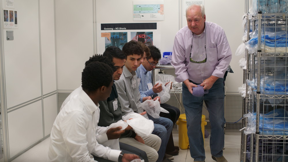 lab staffer with students in a clean room