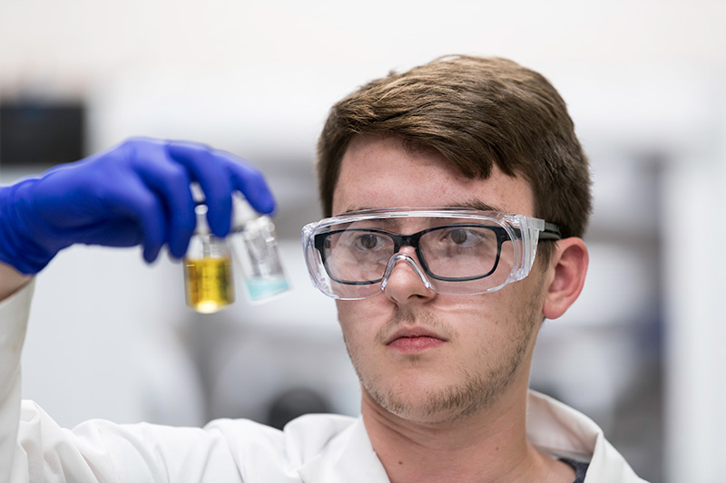 student with lab coat and goggle holding up test tubes