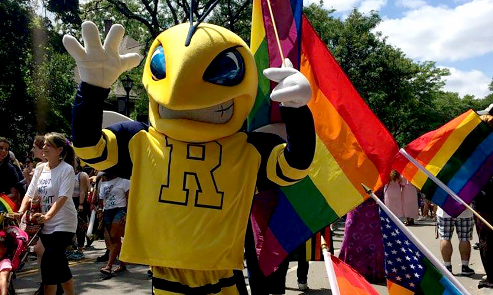 Rocky the Yellowjacket mascot marches in Pride Parade with a rainbow flag