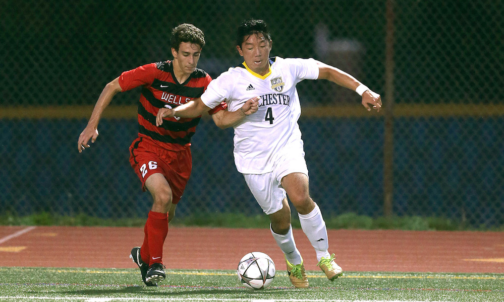 varsity sports soccer players chase a ball