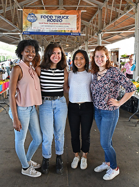 portrait of four students at the Rochester Public Market