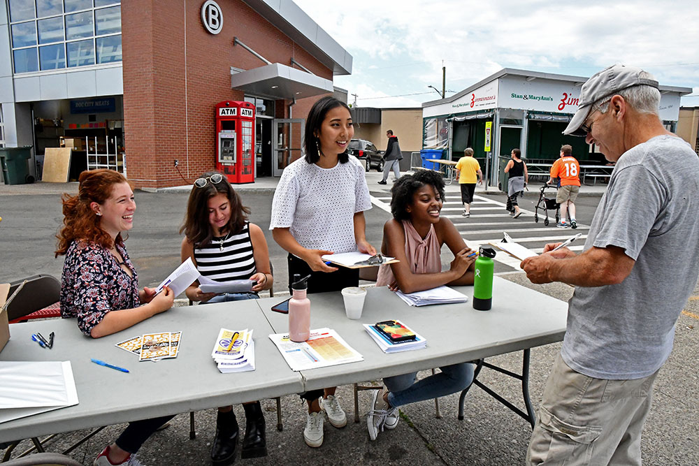 four students sitting behind a table at the public market as one customer fills out a survey