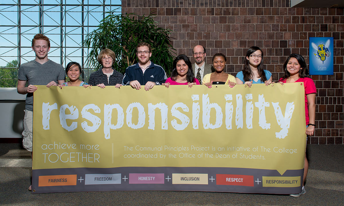 students and staff holding a banner celebrating the Year of Responsibility, one of the University's communal principles