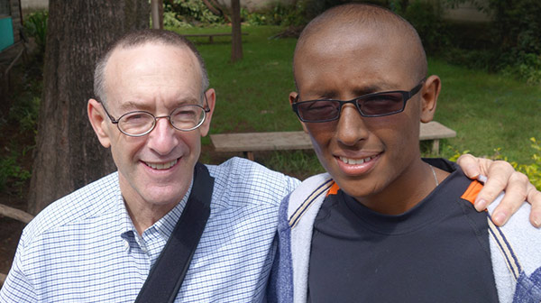 doctor with his arm around his patient, a young man in sunglasses, both smiling
