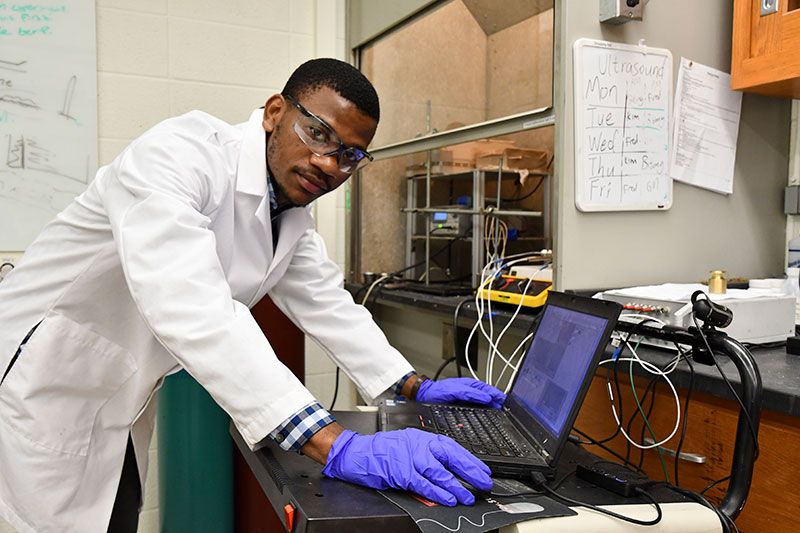 student in a lab coat, working with a laptop