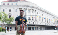 student holding a viola standing in front of Eastman Theatre