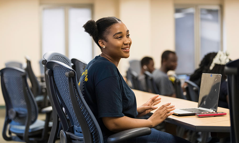 student smiling, sitting at a desk
