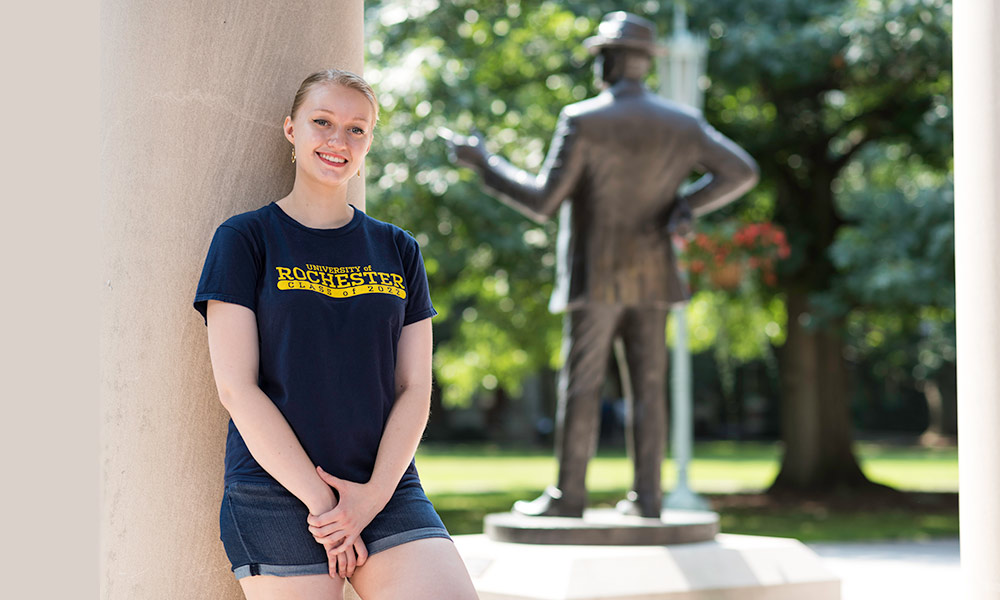 student leaning against a pillar, statue of George Eastman in the background