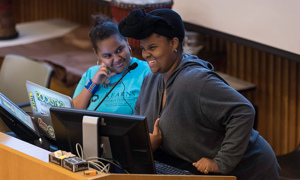 two Upward Bound Rochester students standing at a podium, one with a laptop, one smiling as they speak into the microphone