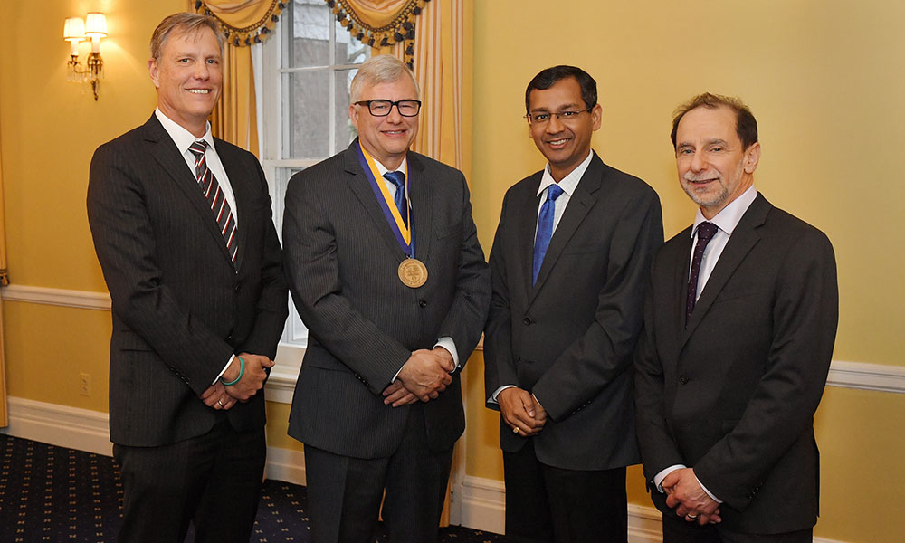 group photo of four people, one with a medallion around his neck