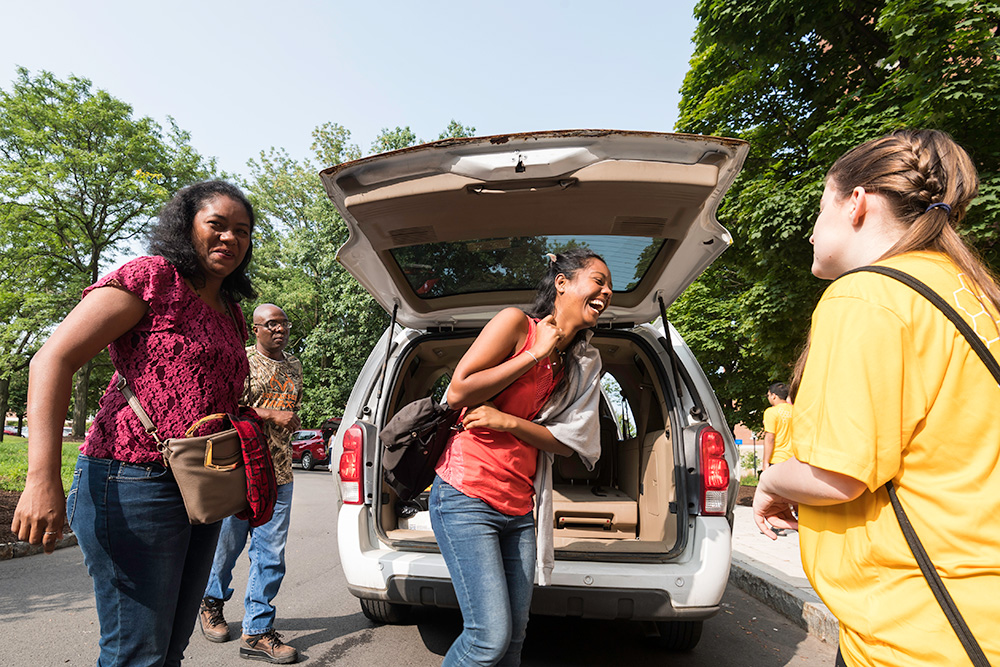 students laughing while unloading luggage from the back of a car