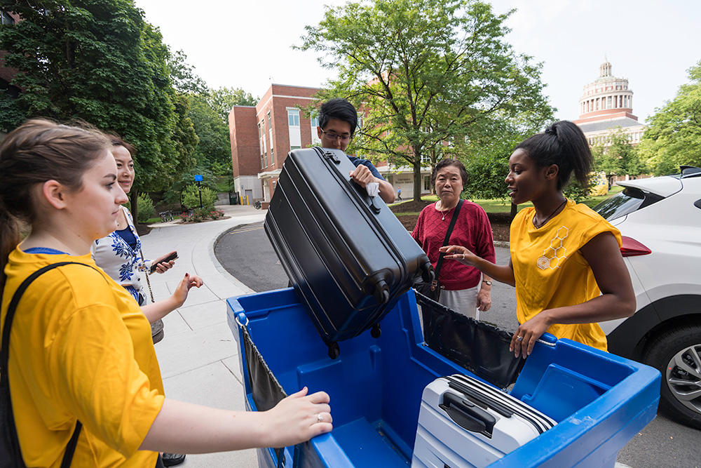group of students removing luggage from a large blue tote