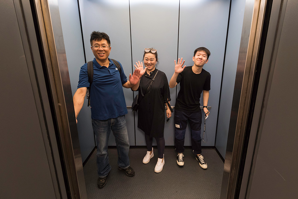 student and his parents wave from inside an elevator
