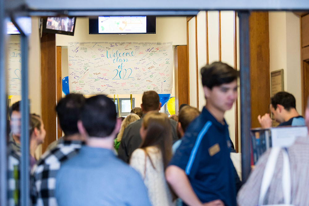 large crowd of students standing under a sign that reads CLASS OF 2022