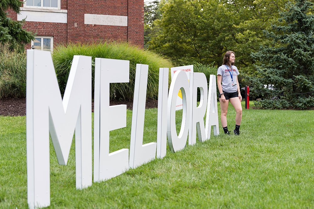 student stands in front of large letters that read MELIORA
