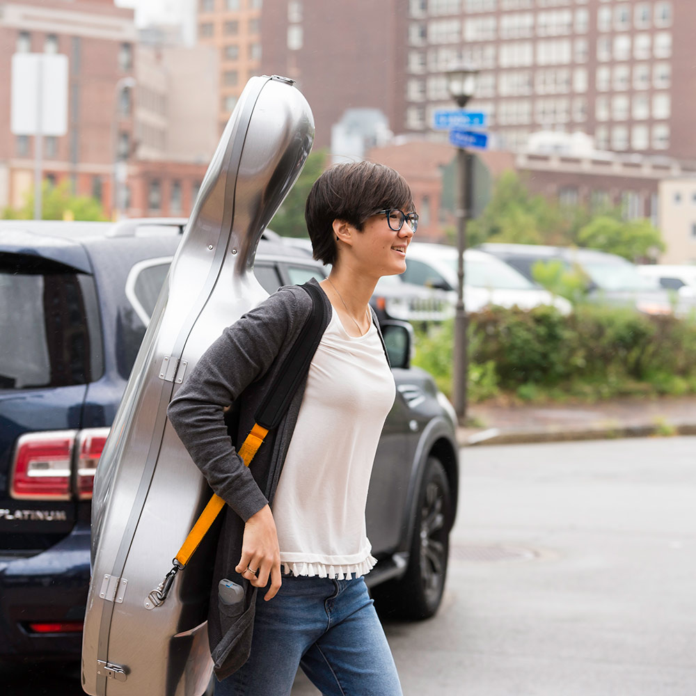 student carrying a large cello case
