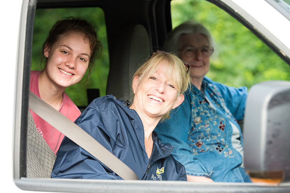 family of three poses for a photo from inside their car