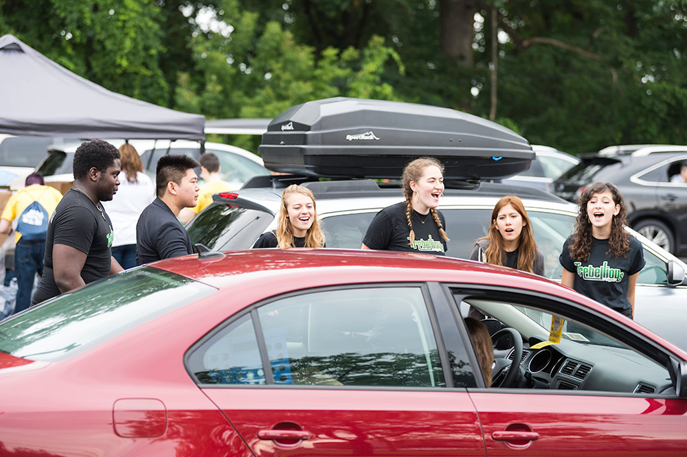 group of students singing for people waiting in a row of cars