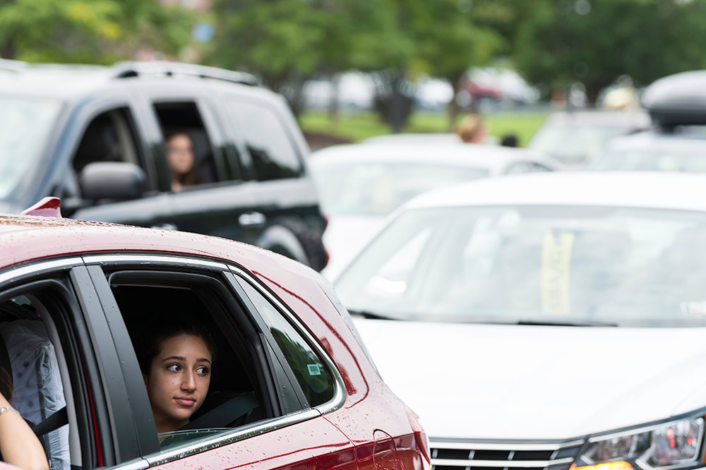 student with a pensive look stares out the window of her parked car