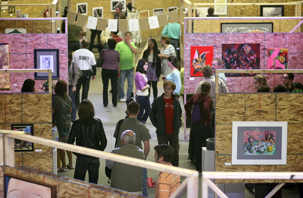 large group of people viewing paintings and other artworks in a large warehouse space
