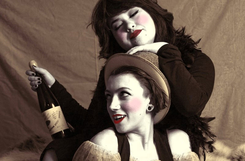 close-up of two artists in costume and makeup, one holding a bottle of wine
