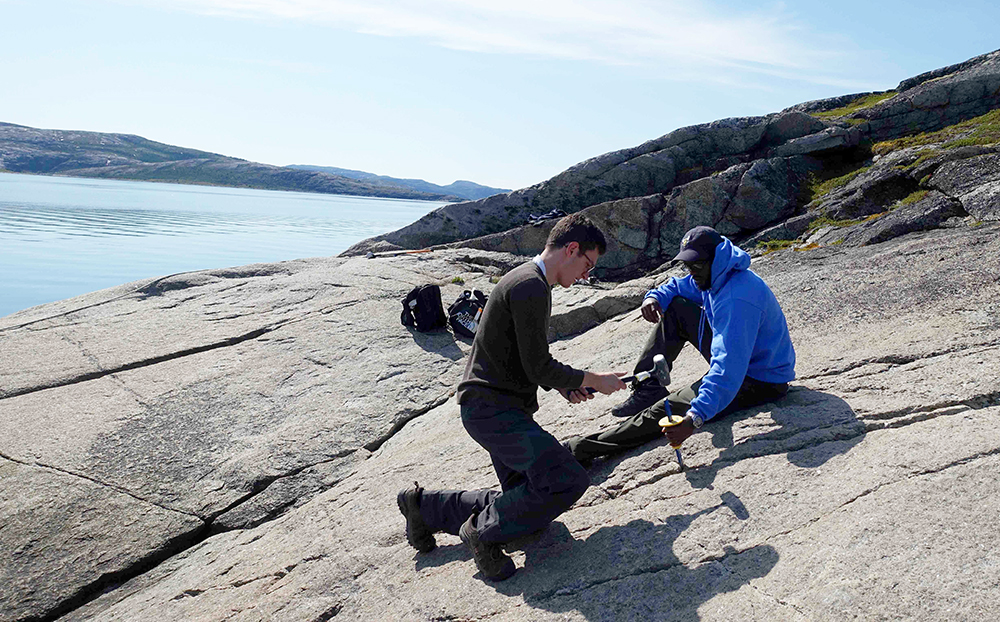 two students on a rock face, using tools to hammer away at the rock surface, with the sun shining on a large body of water in the background