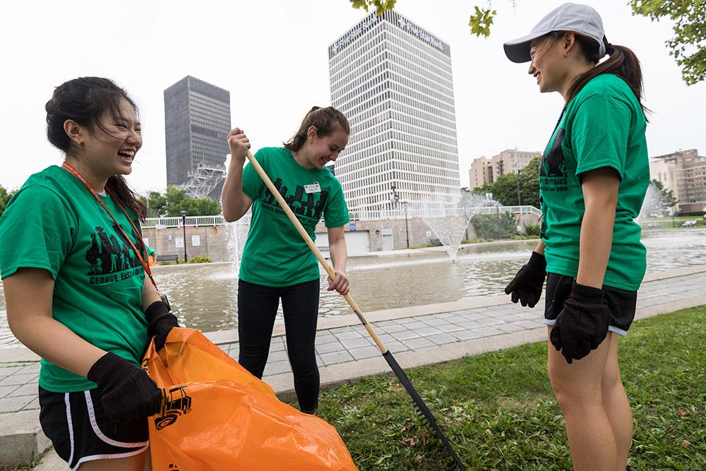 three students raking at a city park