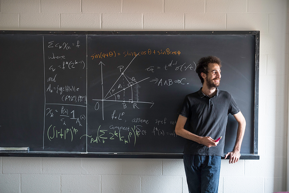 portrait of Nik Chatzikonstanti in front of blackboard with math symbols