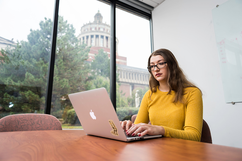 portrait of Wednesday Bushong at laptop with Rush Rhees Library in the background