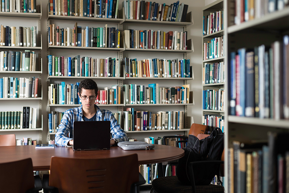 portrait of Yanssel Garcia in front a large bookcase filled with books