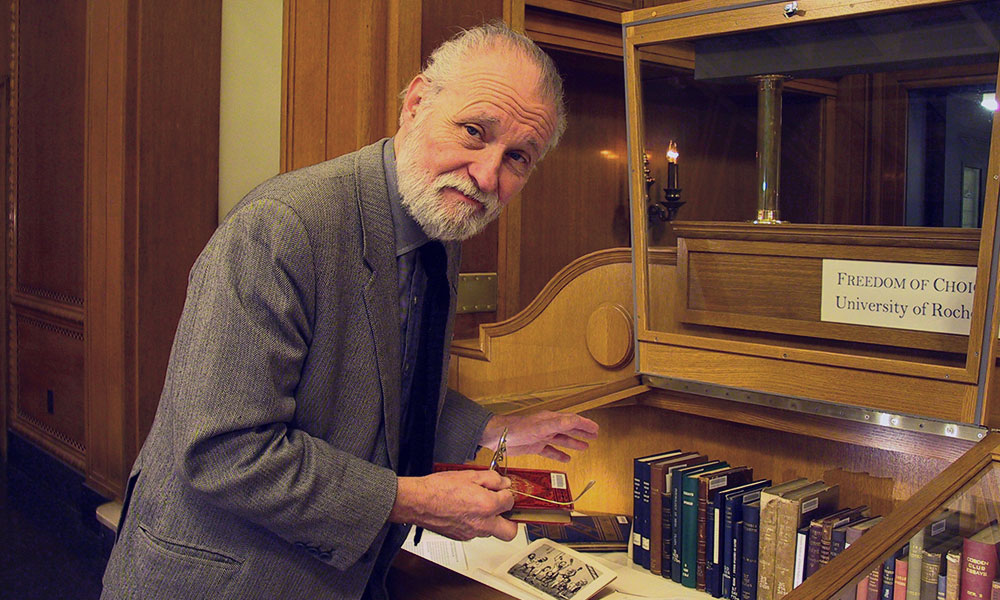historical photo of professor John Waters arranging books in a library case