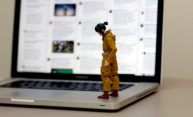 photo of a Star Wars figure/toy of Rose Tico character, standing on the keyboard of a laptop, with a sad expression on her face and a stream of tweets on the laptop screen