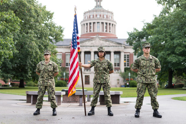 three Navy midshimpen in uniform stand in front of Rush Rhees Library, the one in the center is holding an American flag