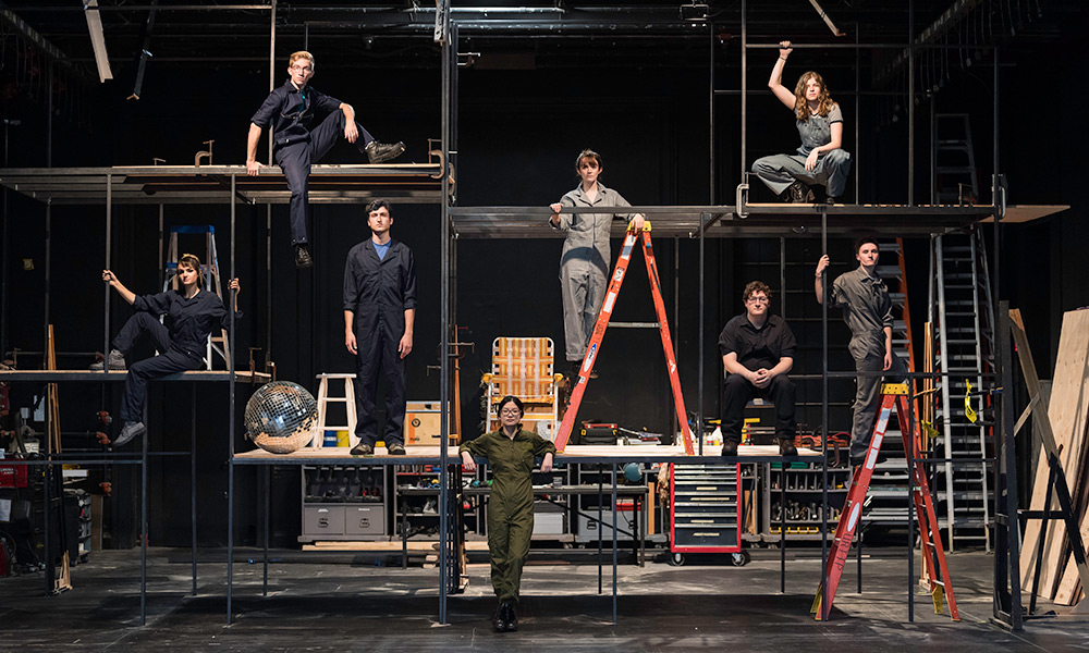 large groups of actors, standing on a tall scaffold on a stage