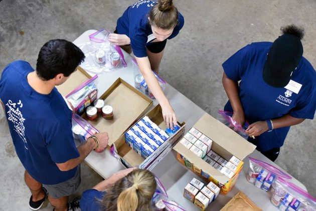 photo looks down from above at four people in matching University of Rochester r-shirts packing boxes with food