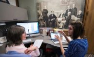 Margaret Becket and Lauren Davis working on computers to transcribe Seward papers