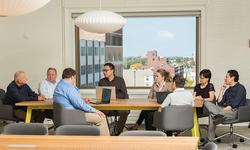 business and science colleagues around a table with the Rochester Data Science Consortium at the Incubator at Sibley Square