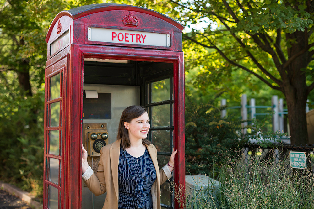 Emily Tworek poses in an English style phonebooth that has the word POETRY written where the word TELEPHONE would be
