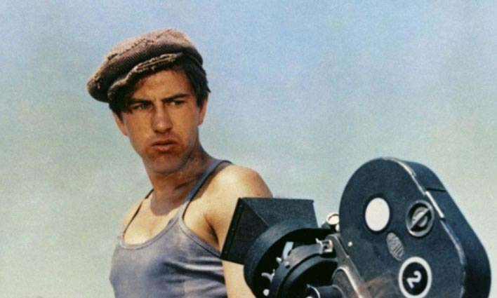 a man in a newsboy cap looking at a 1930s camera