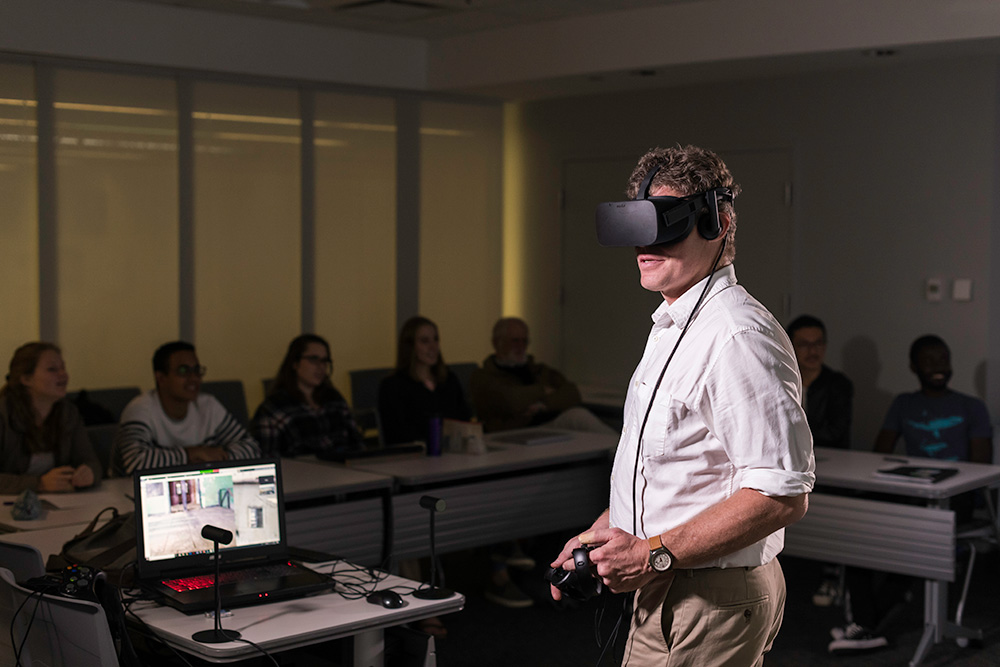Michael Jarvis in front of a classroom of students, wearing a virtual reality headset