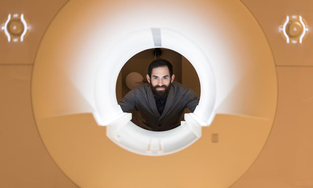 David Dodell-Feder looking through a lighted MRI machine