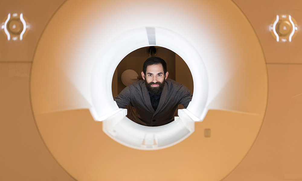 Photo of David Dodell-Feder behind fMRI machine